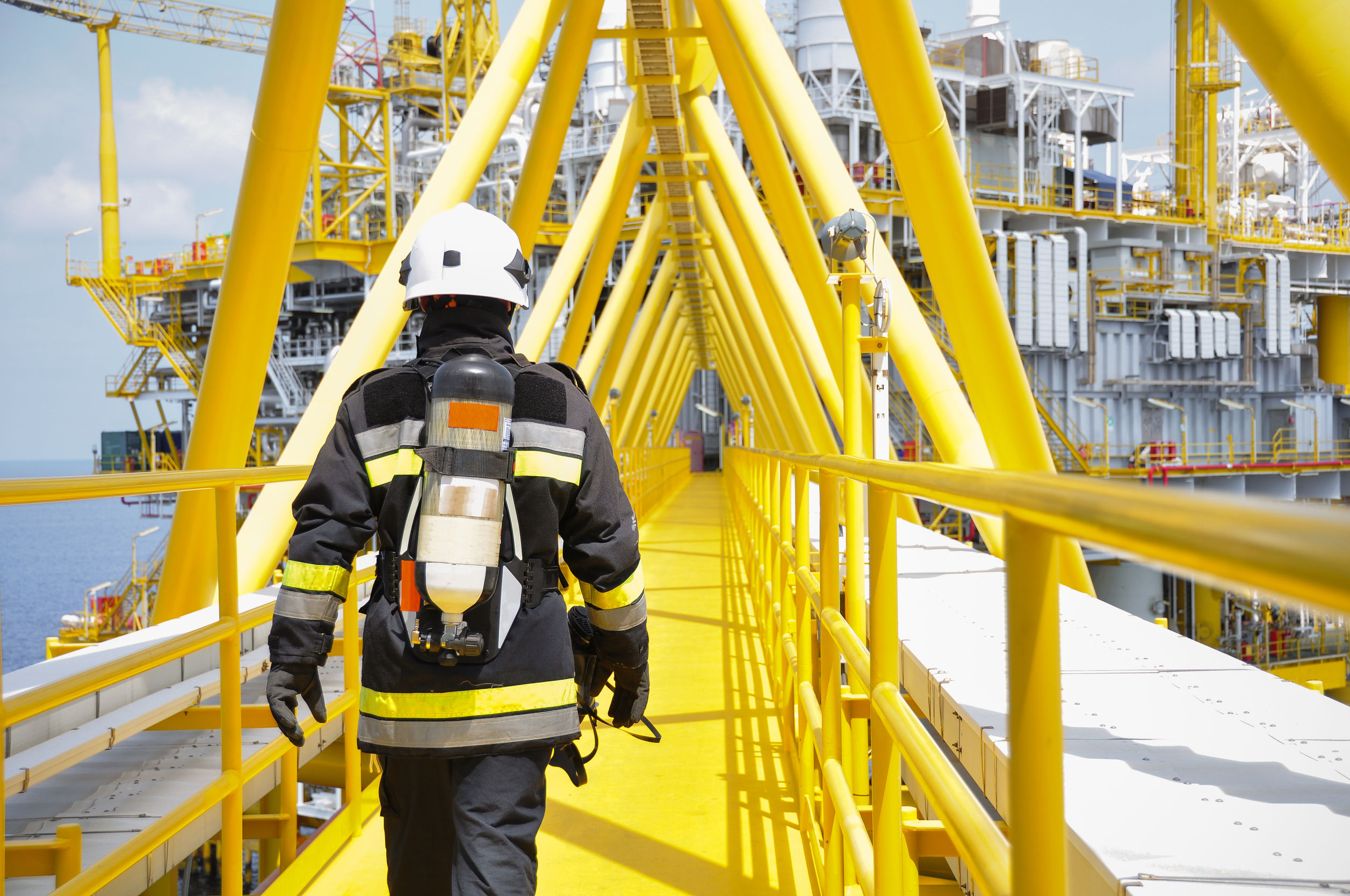 A worker in a uniform walking inside an oil rig to check for loss prevention services.