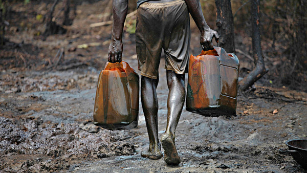 A labour carrying two oil containers in both the hands gas.
